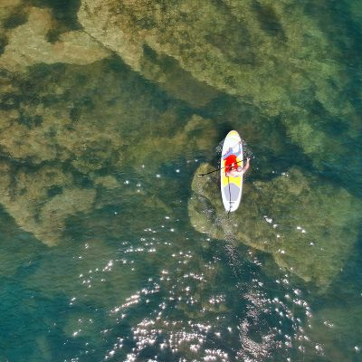 A top-down view of a man paddleboarding