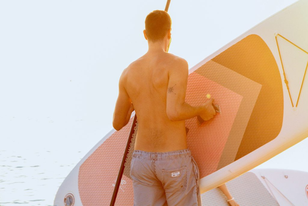 A man carrying a paddleboard